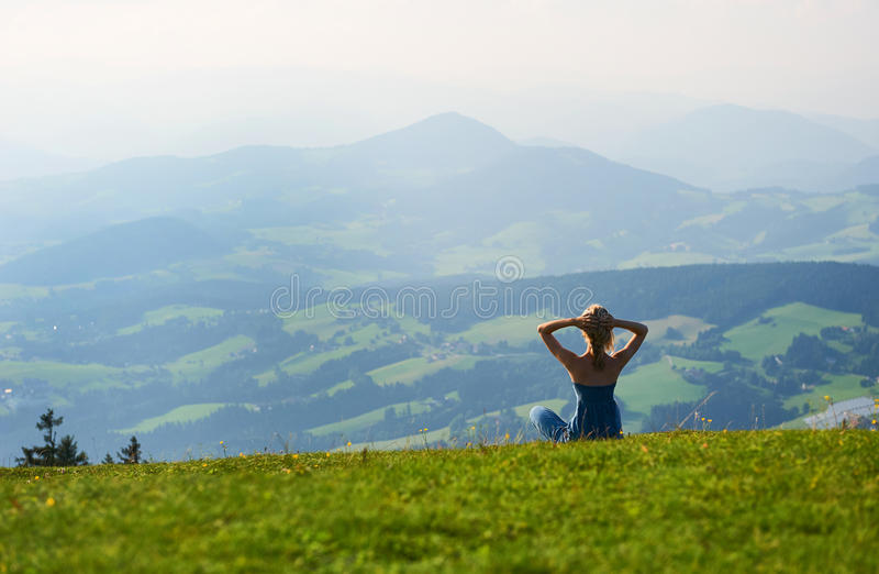 Woman sitting on mountain top. stock image