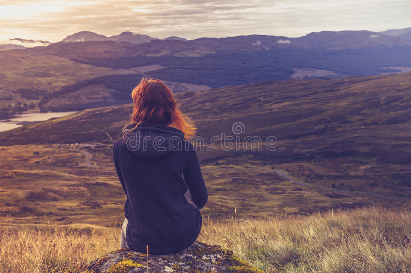 Woman sitting on mountain top and contemplating royalty free stock photography