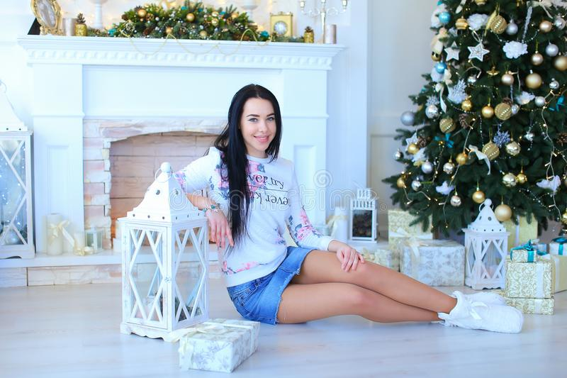 Woman sitting near decorated white fireplace and Christmas tree. royalty free stock photography