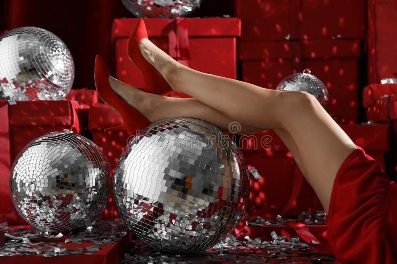 Woman sitting near disco balls on red Christmas gifts indoors royalty free stock images