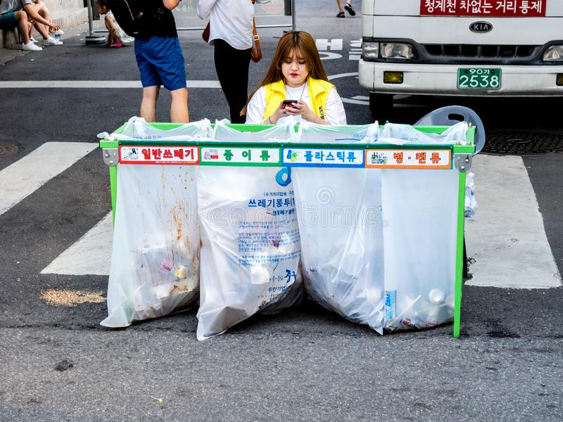 Woman sitting near waste sorting containers with colored inscriptions for plastic, glass bottles and paper in downtown in Seoul. Seoul, South Korea - June 17 royalty free stock photography