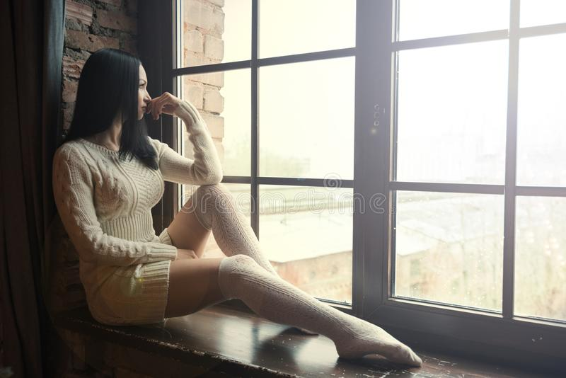 Woman sitting near window and looking outside. royalty free stock image