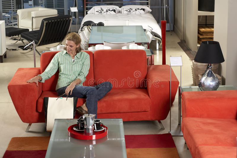 Woman sitting on new red sofa in furniture store, stroking armrest, holding shopping bags, smiling stock images
