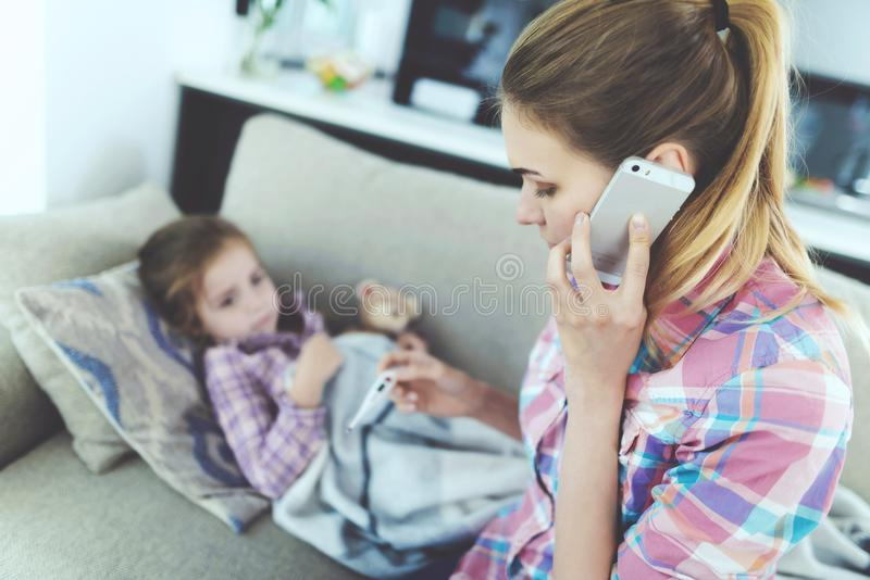A woman is sitting next to a little girl who is sick. She holds a thermometer, which the girl`s temperature measured. stock photos