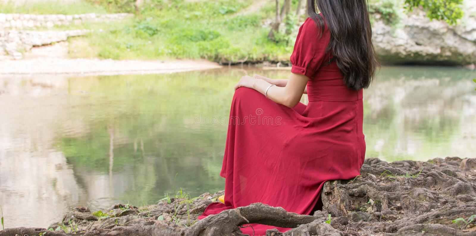 Woman sitting next to a river alone. Fashionable woman sitting next to a river alone royalty free stock image