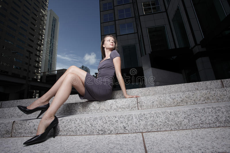 Woman sitting by an office building royalty free stock photo