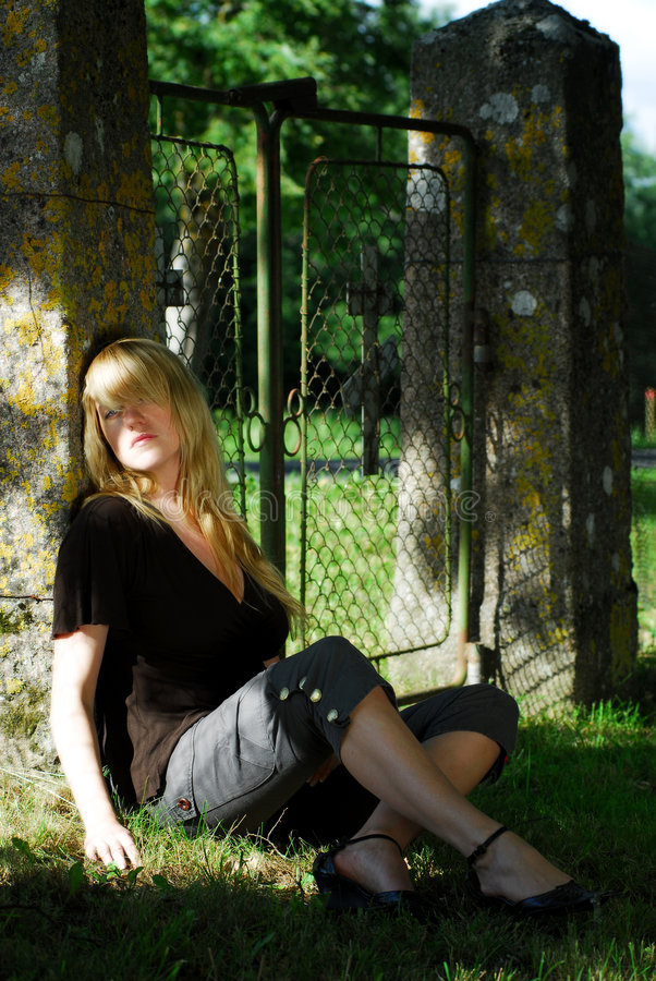 Woman sitting by old gate stock images