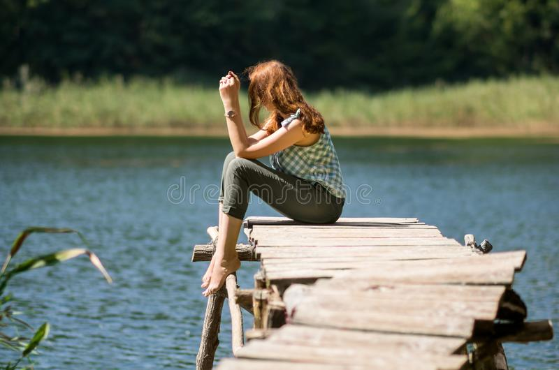 Woman sitting on a wooden bridge royalty free stock photography