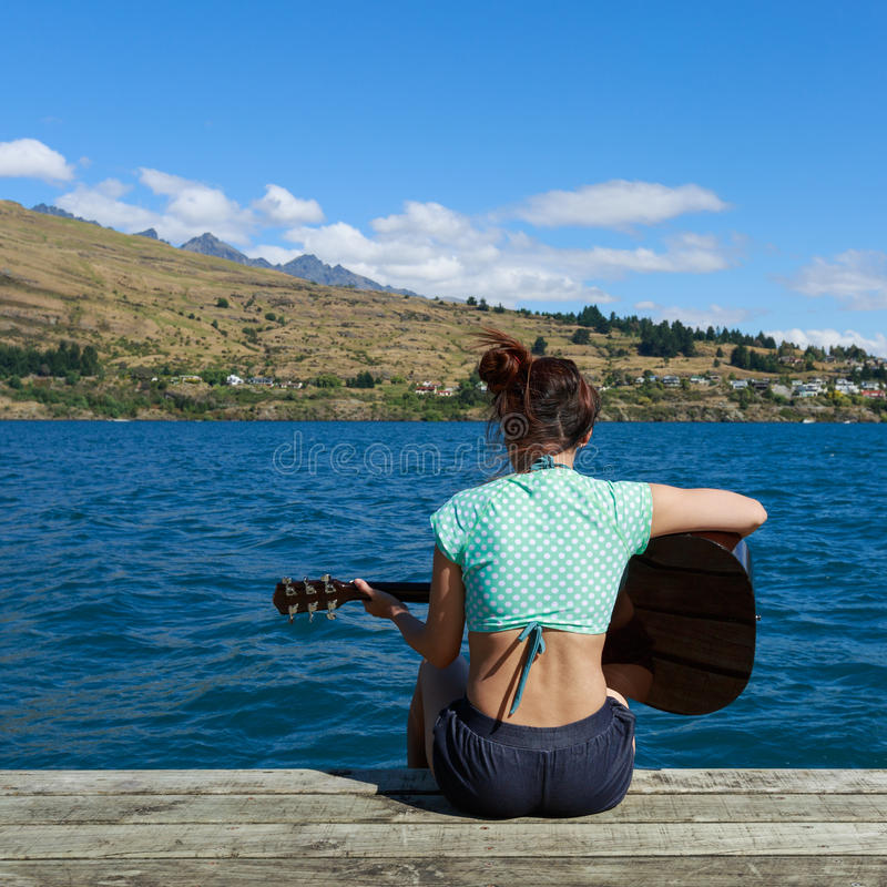 Free Woman Sitting On Pier And Playing Guitar Stock Images - 64102214