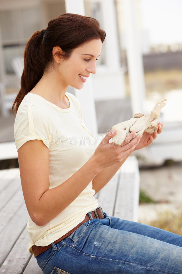 Woman Sitting Outdoors Holding Starfish Stock Images