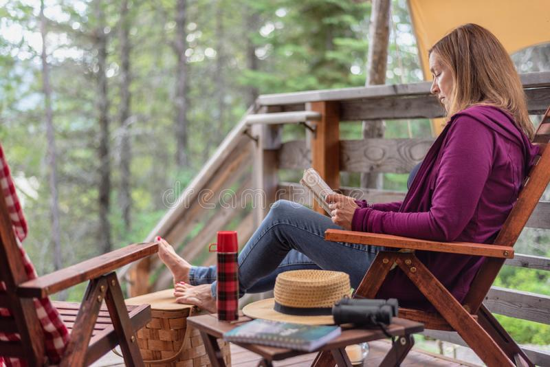 Woman sitting outside cabin in woods relaxing with a book stock images