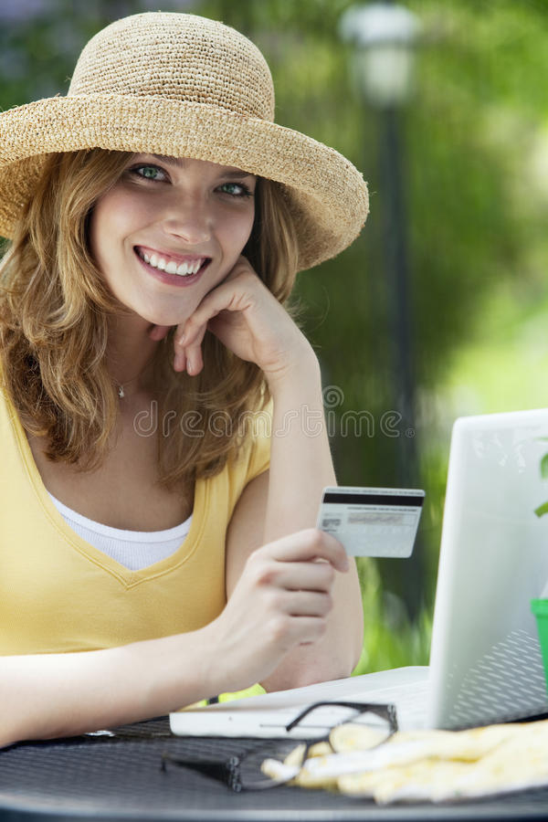 Woman Sitting Outside Using Credit Card And Laptop Stock Photo