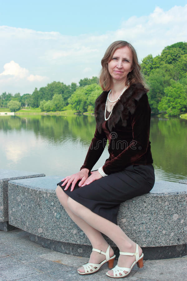 Download A Woman Is Sitting On The Parapet Near The Pond Stock Image - Image: 31611281