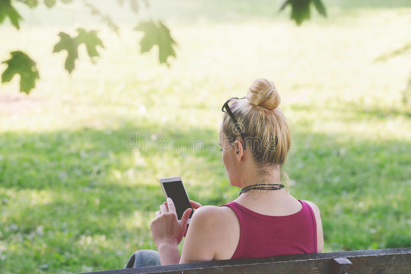 Woman sitting on a park bench , texting on her phone royalty free stock images
