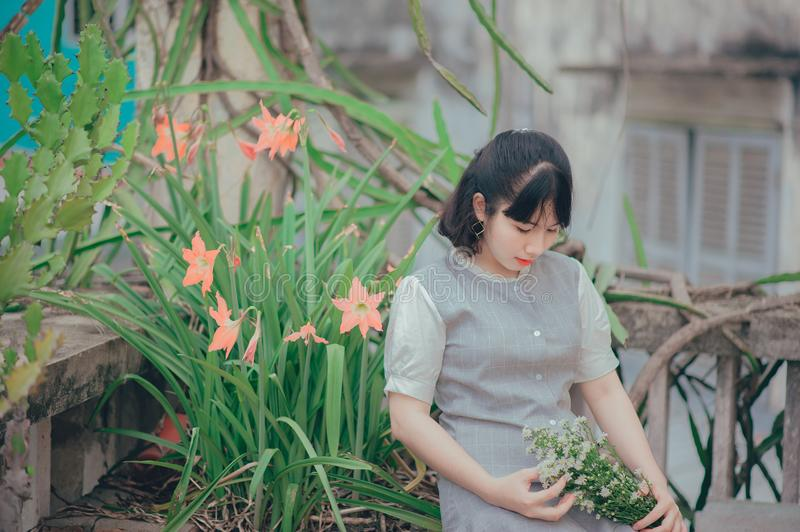 Woman Sitting Beside Pink Petaled Flower While Holding Bouquet of Flower stock photos