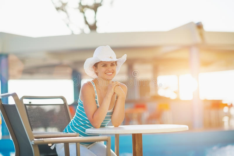 Woman sitting at pool bar. Happy young woman sitting at pool bar stock photography