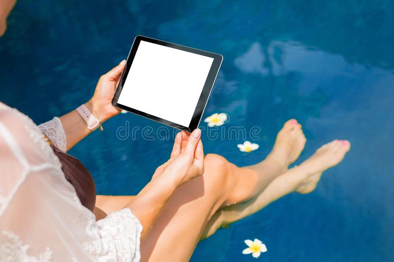 Woman sitting by the pool and using tablet computer. Horizontal screen orientation. royalty free stock photography