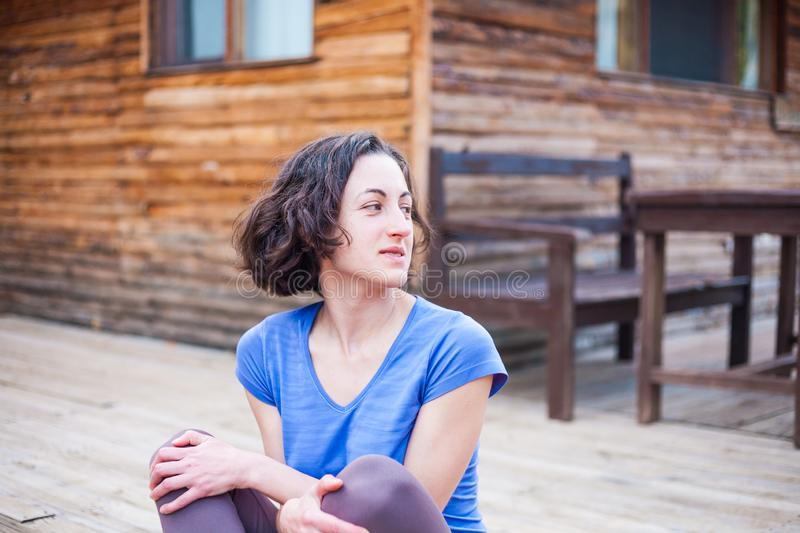 A woman is sitting on the porch of an old wooden house royalty free stock image