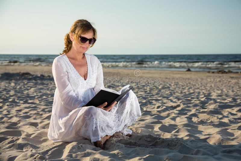 Woman sitting and reading book on beach stock images