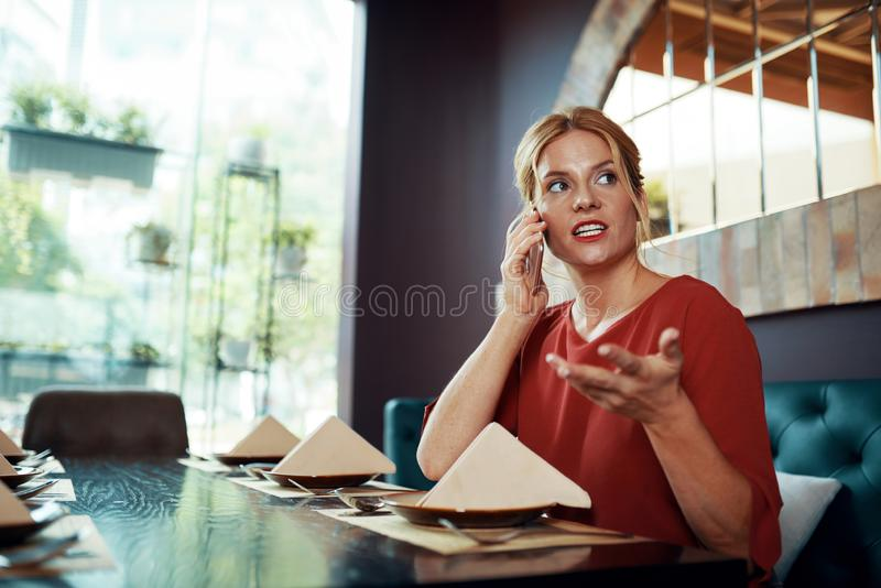 Woman sitting at restaurant and talking on phone stock photos