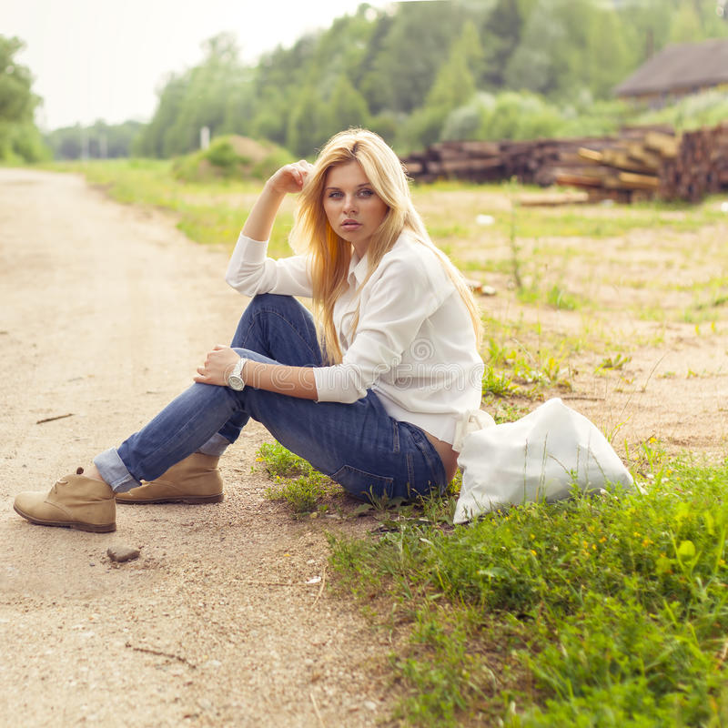 The woman sitting beside the road with a bag stock photo