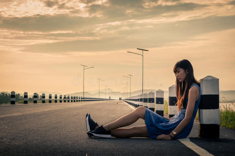 Woman sitting on the road. Lonely woman sitting on the road stock photo