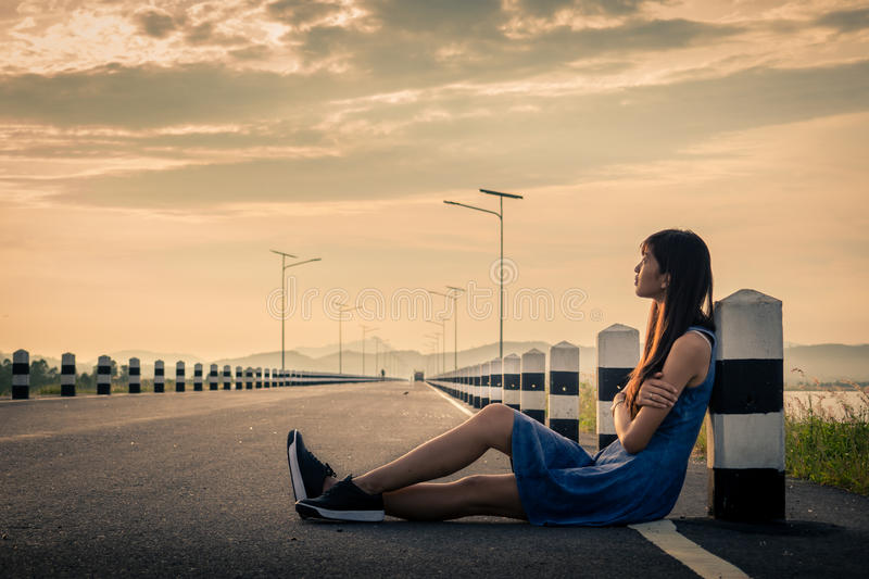 Woman sitting on the road. Lonely woman sitting on the road stock photography