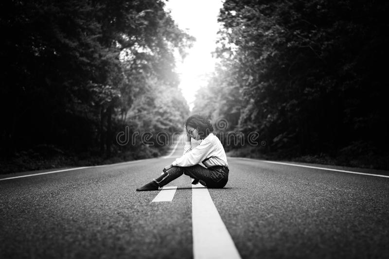 Woman sitting on road waiting for car stock photos
