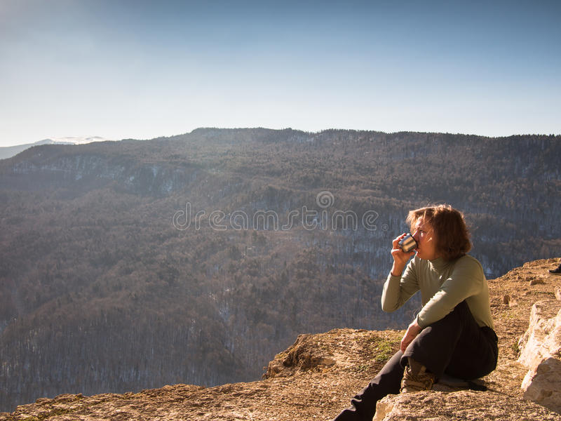 Woman sitting on a rock and drinking from a cup stock photos