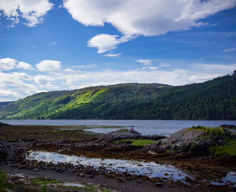 Woman sitting on a rock looking off into the distance in Scotland. Woman sitting on a rock looking off into the distance to a picturesque landscape in Scotland stock images