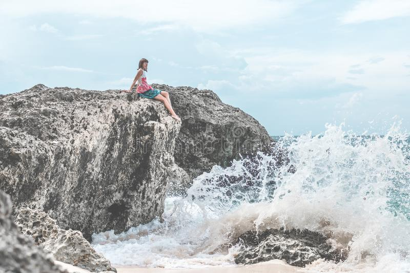 Woman Sitting of Rock Near Body of Water royalty free stock image