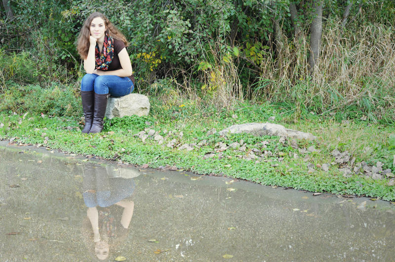Woman Sitting on Rock Reflection royalty free stock images