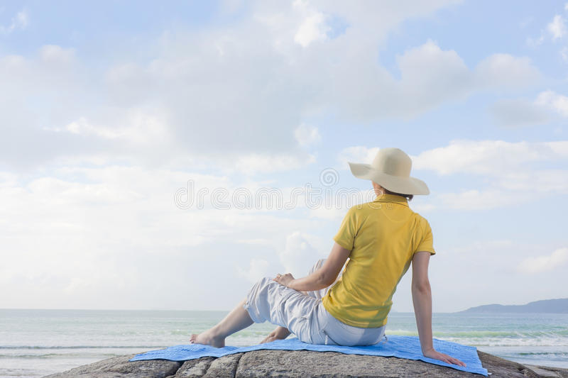 Woman sitting on a rock at the sea stock photography
