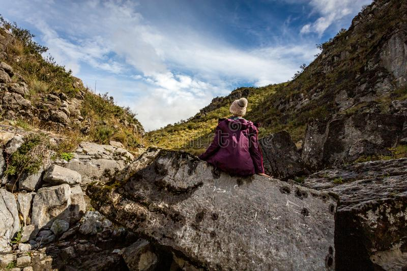 Woman sitting on rock with sea fossils more than 1200 mtrs above sea royalty free stock photos