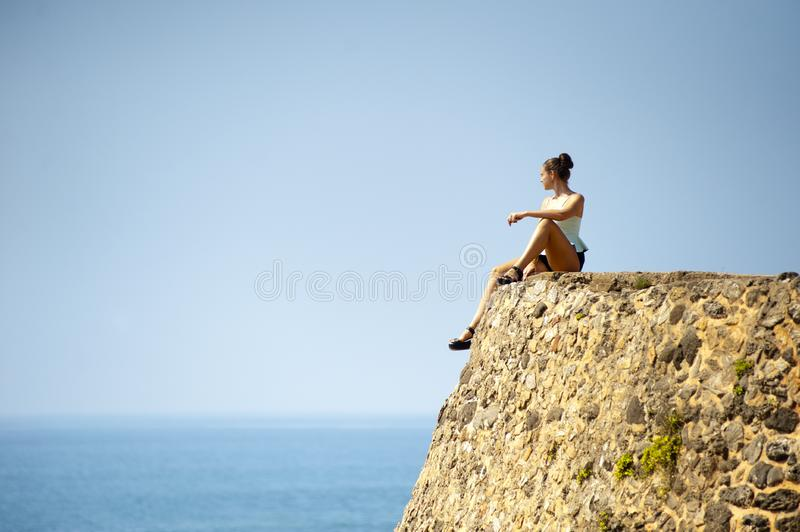 Woman sitting on rock by sea stock photos