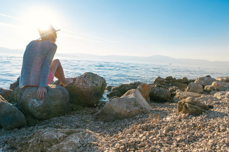 Woman sitting on rocks by the sea royalty free stock image