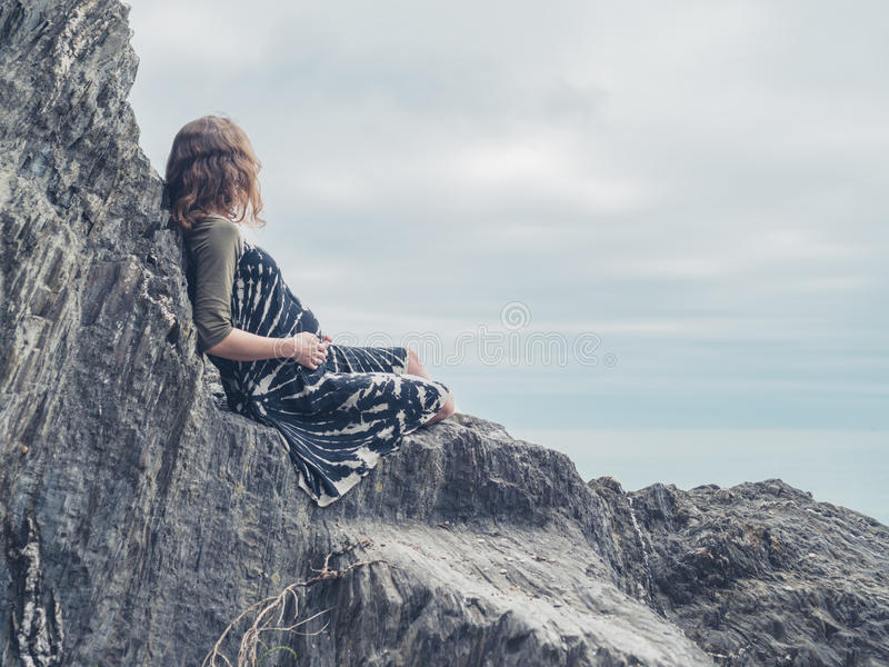 Woman sitting on rocks by the sea. A young woman is sitting on some rocks by the sea royalty free stock images