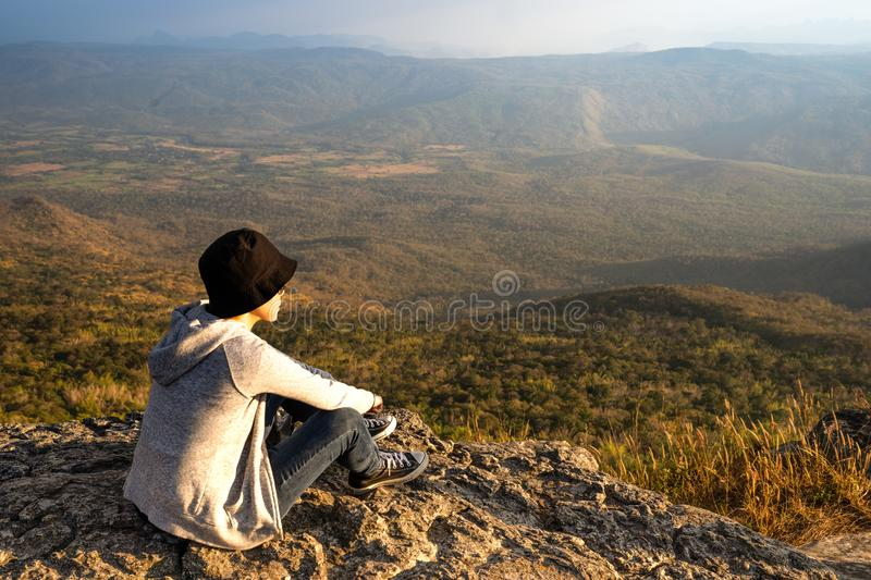 A woman sitting on rocky mountain looking out at scenic natural view and beautiful blue sky royalty free stock image