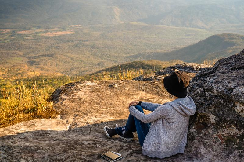A woman sitting on rocky mountain looking out at scenic natural view and beautiful blue sky royalty free stock photography