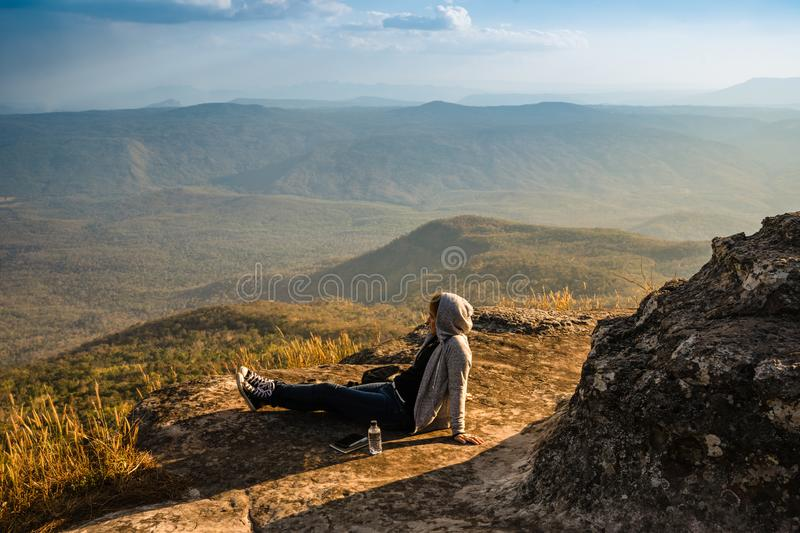 A woman sitting on rocky mountain looking out at scenic natural view and beautiful blue sky royalty free stock images