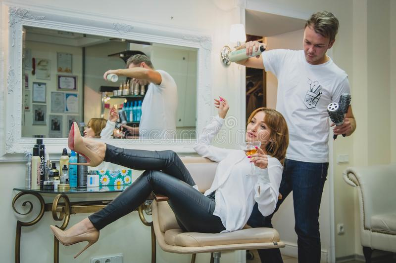 Woman Sitting on the Salon Chair While Holding Vodka Glass and Man at Her Back White Spraying Her Hair royalty free stock photography
