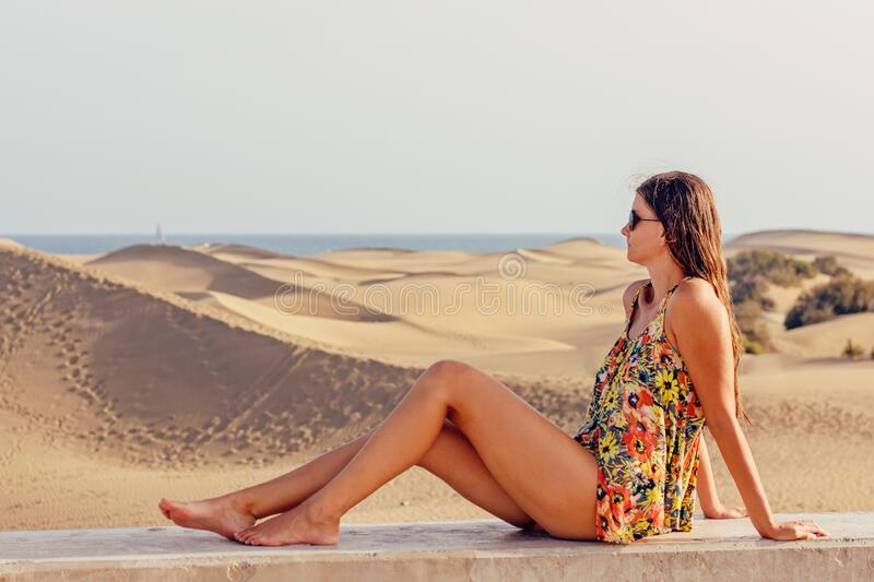 Woman Sitting on Sand at Beach Against Sky royalty free stock photography