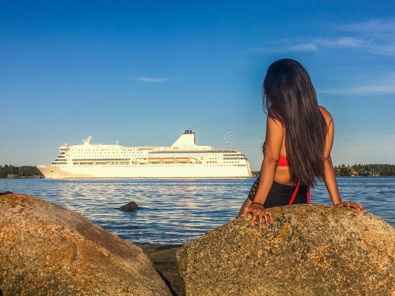 Woman Sitting By The Sea Watching A Cruise Ship  royalty free stock images