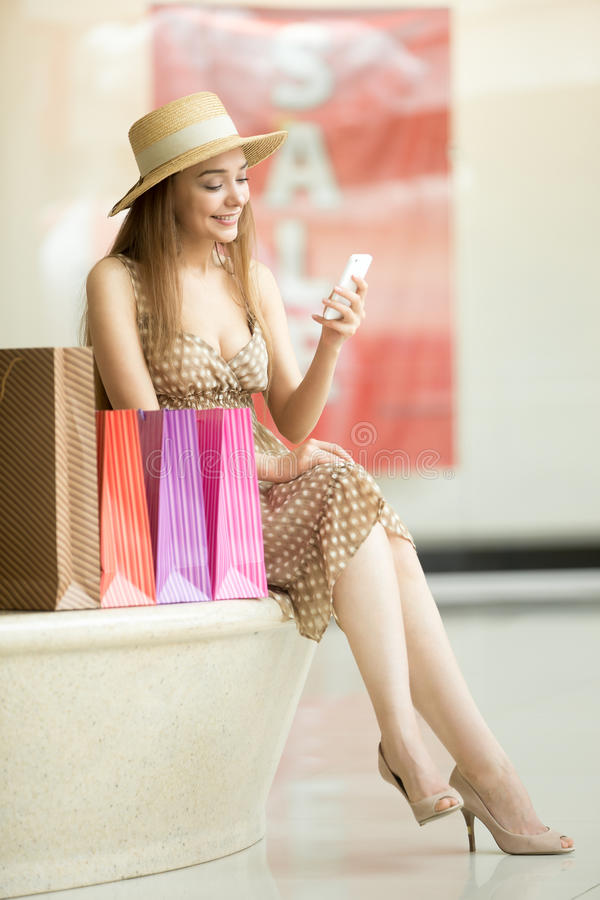 Woman sitting in shopping centre with mobile phone smiling. Beautiful happy woman wearing hat and dress sitting with legs crossed in shopping centre near stock image