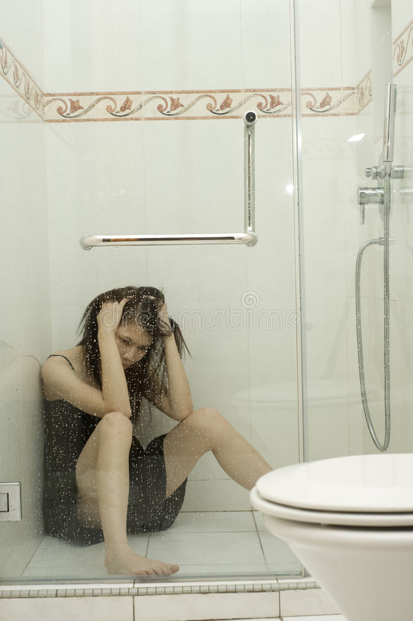 Woman sitting in shower stock photo