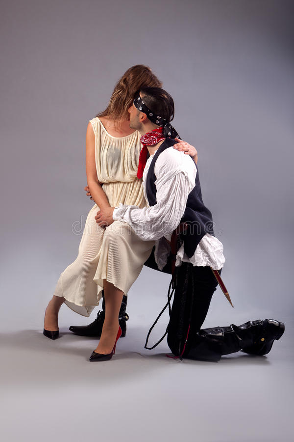 Woman sitting shy on knee man pirate stock photography