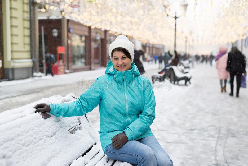Woman is sitting on snow-covered bench in street of Moscow, Russia. Woman is sitting on a snow-covered bench in the street of Moscow, Russia stock image