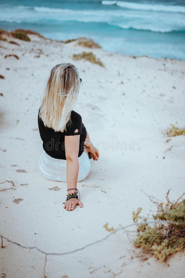 Woman sitting in snow-white dune landscape on the Atlantic coastline. Sao Vicente Cape Verde.  royalty free stock photos