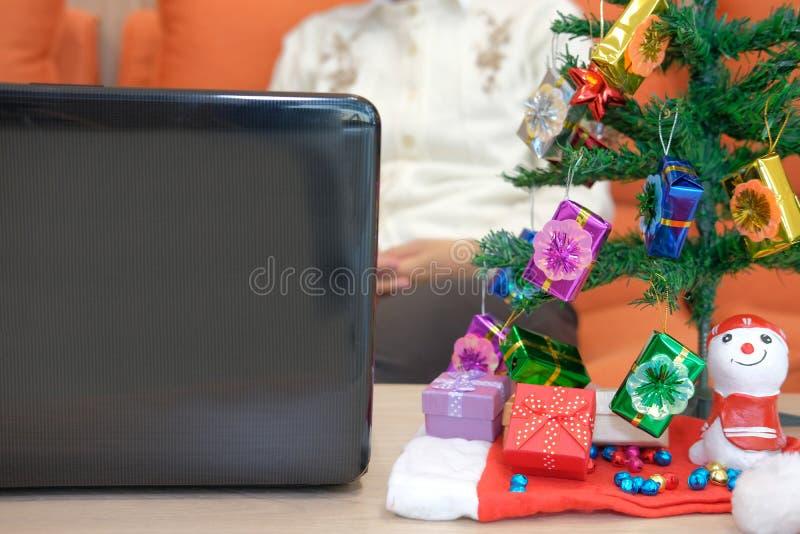 Woman sitting on sofa with gift box christmas tee. xmas new year. Woman sitting on sofa at home with gift box christmas tee. xmas new year celebration royalty free stock photography