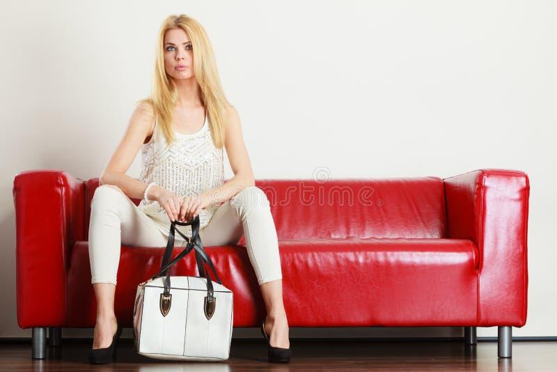 Woman sitting on sofa holding white bag stock photos